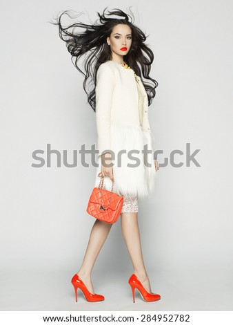 Beautiful brunette model in fashion clothes posing in studio. Wearing coat, handbag, red shoes - stock photo