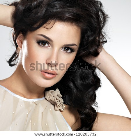 Beautiful brunette model with long curly brown hair. Pretty model poses at studio. - stock photo