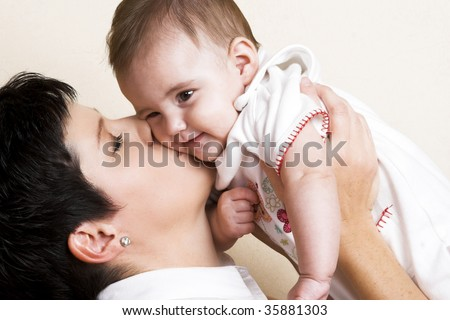 Beautiful brunette mother holding her cute baby - stock photo