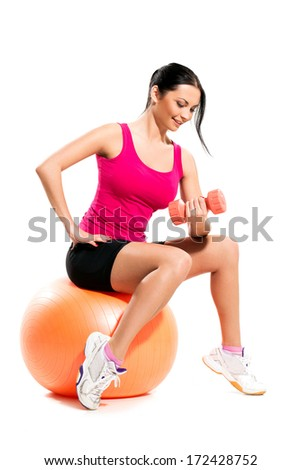 Beautiful brunette on the ball with a dumbbell - stock photo