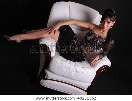 beautiful brunette on white leather armchair - stock photo