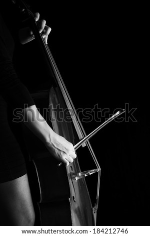 Beautiful brunette playing a cello with selective light in black dress artistic conversion