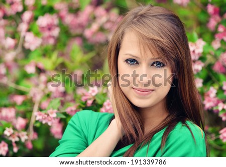 beautiful brunette posing against spring flowers - stock photo