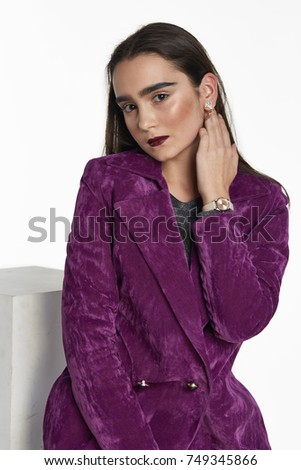 Beautiful brunette posing in gray blouse and purple coat