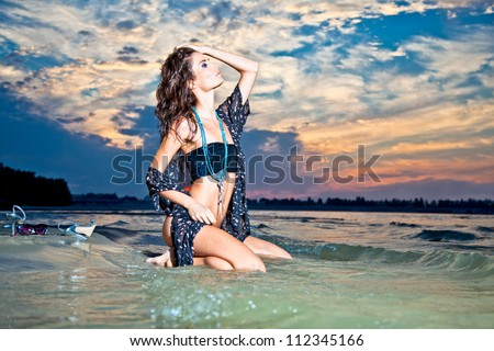 Beautiful brunette posing  on river bank in sunset. Art photo. - stock photo