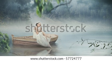 Beautiful brunette posing over beautiful romantic landscape - panoramic version - stock photo