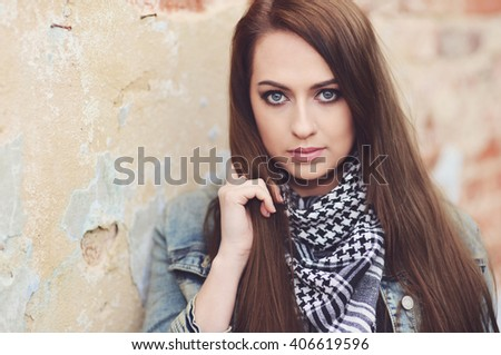 Beautiful brunette posing over stone wall
