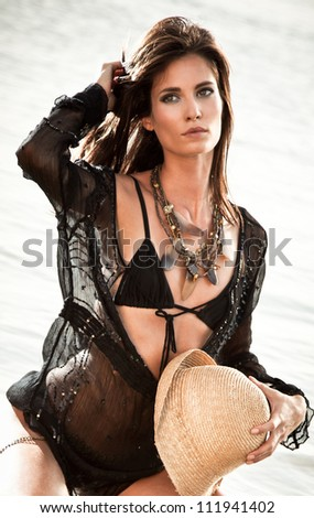 Beautiful brunette posing with river behind. Art photo. - stock photo