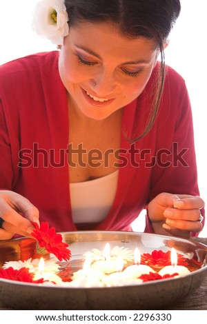 Beautiful brunette putting a new flower in the bowl with floating candles and flowers - stock photo