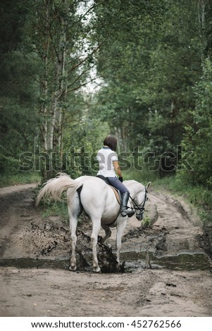 Beautiful brunette riding her white horse in the summer forest while the horse is jumping in a huge mud paddle - stock photo
