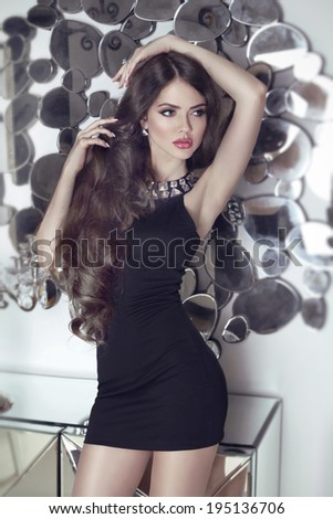 Beautiful brunette sensual girl model in short black dress posing mirrors wall - stock photo
