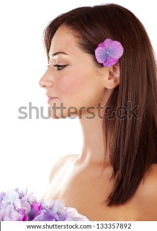 Beautiful brunette sensual woman enjoying day spa, side view of attractive young female with purple flowers isolated on white background - stock photo
