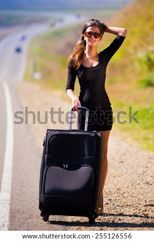 beautiful  brunette  sexy  woman in black dress and sunglasses  go road and holds suitcase  has long hair  and elegant body - stock photo