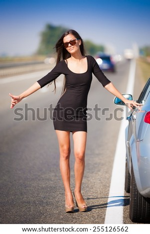 beautiful  brunette  sexy  woman in black dress and sunglasses  has the broken car and  long hair  and elegant body - stock photo