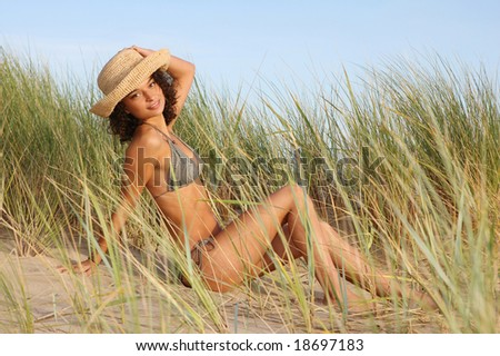 Beautiful brunette sitting in sand dunes