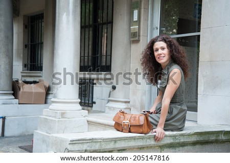 Beautiful brunette sitting on a porch with leather bag nearby - stock photo