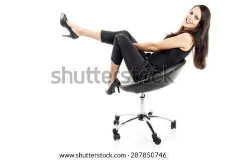 Beautiful brunette sitting on black chair.  - stock photo