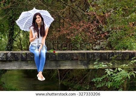 Beautiful brunette sitting on bridge holding white lace umbrella. - stock photo