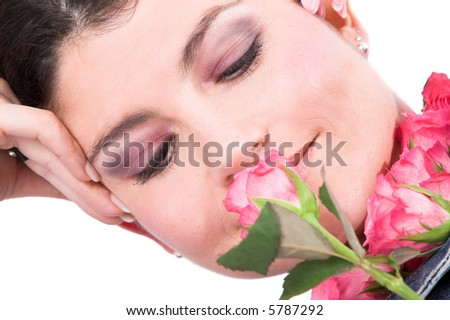 Beautiful brunette smelling a rose while leaning on her arm - stock photo