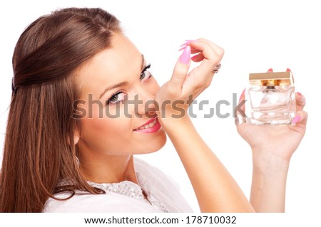 Beautiful brunette smelling perfume from her hand and looking at camera, isolated on white - stock photo