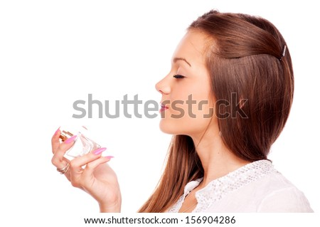 Beautiful brunette smelling perfume, isolated on white - stock photo