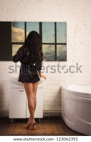 Beautiful brunette spa woman in the bathroom