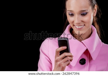 Beautiful brunette talks by mobile phone, is isolated on black background. - stock photo