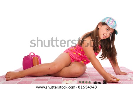 beautiful brunette teenage girl in swimsuit at the beach playing with little stones (studio setting with towel, bag and sun lotion, isolated on white background) - stock photo