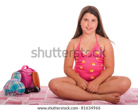 beautiful brunette teenage girl in swimsuit at the beach (studio setting with bag, cap, towel, sun lotion, sunglasses) isolated on white background - stock photo