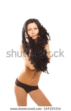 Beautiful brunette topless in a black panties posing on the white background, in the studio, she has her breasts hidden under black feathers, glamour photography - stock photo