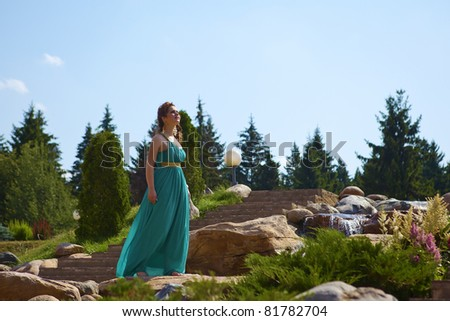 beautiful brunette walking in the park next to a small waterfall - stock photo