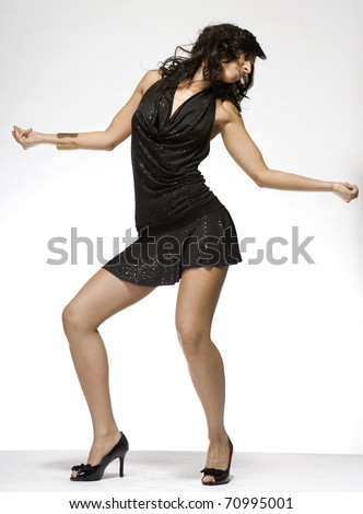 beautiful brunette wearing black dress on light background - stock photo