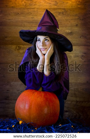 beautiful brunette witch in ? purple hat and with a huge pumpkin