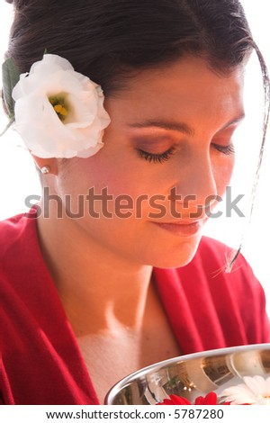 beautiful brunette with a bowl filled with small candles closing her eyes - stock photo