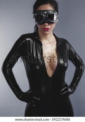 beautiful brunette with black suit, armed and dangerous latex, sensuality and slim body - stock photo