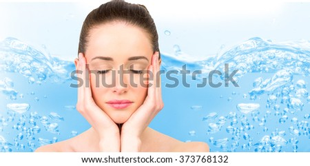 Beautiful brunette with eyes closed against close up on blue sparkling water - stock photo