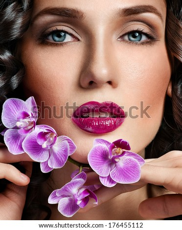 beautiful brunette with gorgeous curly hair and  orchid flower - stock photo
