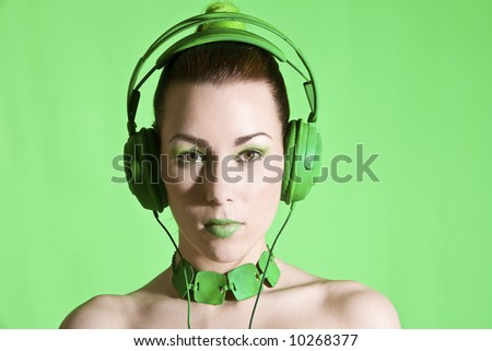 Beautiful brunette with headphone on green background - stock photo