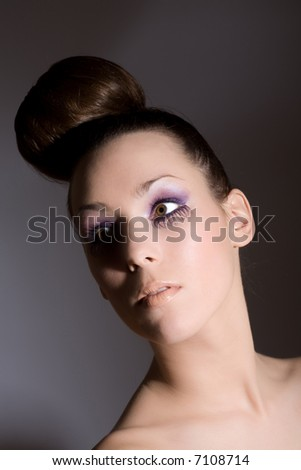 Beautiful brunette with her hair in a knot and purple eyelashes - stock photo