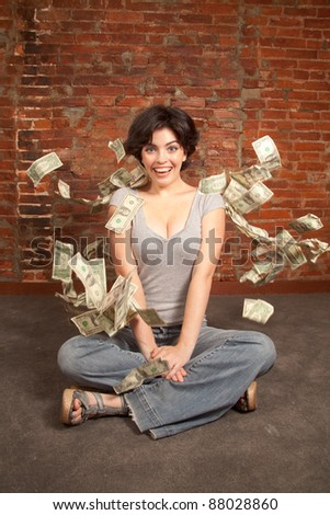 Beautiful brunette  with hundred and twenty dollars bills falling around her - stock photo