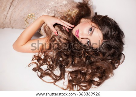Beautiful brunette with long curly hair and gorgeous beige lace dress lying on a white background. Perfect hair and skin. Vogue stile. Beauty concept
