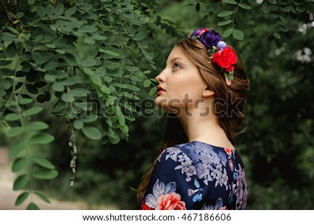 beautiful brunette with long hair and blue eyes, wearing a wreath of flowers and a dress with floral print. close-up portrait of a young girl.