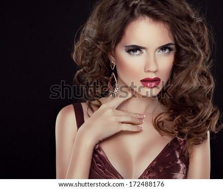 Beautiful brunette with long wavy hair. Professional makeup. Hairstyle. Elegant lady  isolated on dark background