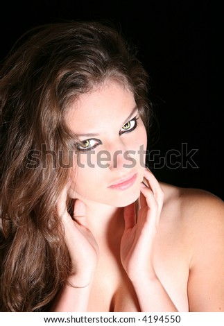 Beautiful brunette with wolf eyes on black background - stock photo