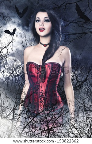 Beautiful brunette woman as sexy vampire - halloween portrait - stock photo
