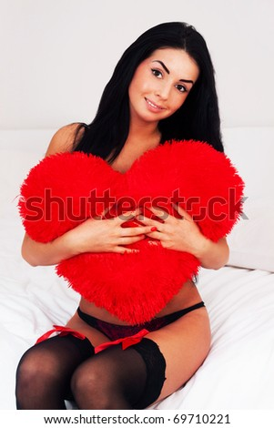 beautiful brunette woman at home hugging a big fluffy soft heart. feast day of St. Valentine - stock photo