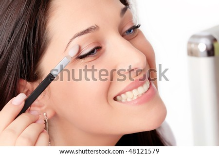 Beautiful brunette woman doing makeup - stock photo