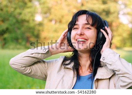 Beautiful brunette woman enjoys the music in headphones outdoors on the meadow - stock photo