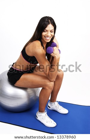 Beautiful brunette woman exercising on a blue mat with purple dumbbells - stock photo