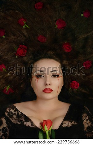 Beautiful brunette woman holding rose and with roses in her hair crying blood. Fantasy woman. Book cover - stock photo
